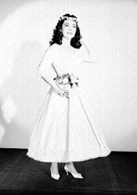 Judith Sierra, de pie y de frente con vestuario teatral y ramo en mano, retrato