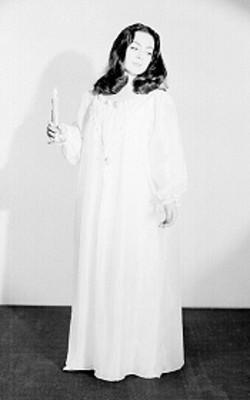 Judith Sierra, de pie con vestuario teatral y vela encendida en mano derecha, retrato