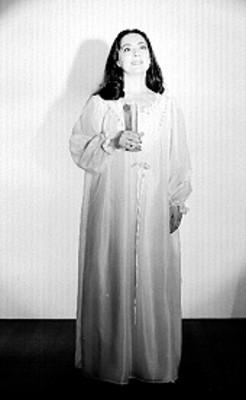 Judith Sierra, de pie y de frente, con vstuario teatral y vela en mano, retrato