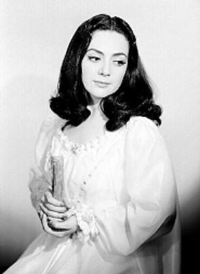 Judith Sierra, sentada, vista a su izquierda, con vestuario teatral, retrato