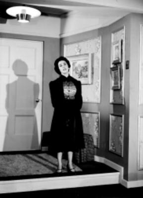 Mujer de pie con bolso en manos, escena de la obra Los Excluidos del Cielo, retrato