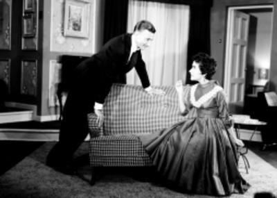 Mujer sentada observa a un hombre apoyado en el respaldo de sofa, escena de la obra Los Excluidos del Cielo