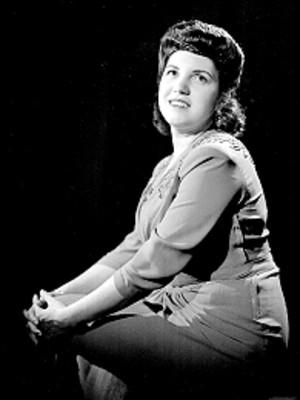 Irma Gonzalez sentada de perfil, con rostro al frente, retrato