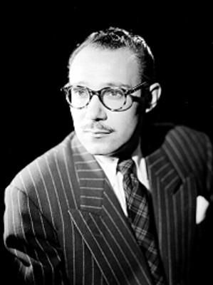 Jose Riquelme, en tres cuartos de perfil, viste formal y usa anteojos, retrato