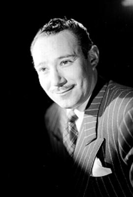 Jose Riquelme, sonríe, con rostro resaltado y fondo oscuro, retrato