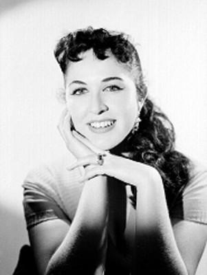 Maria Rubio, sonríe de frente con manos en la mejilla, retrato