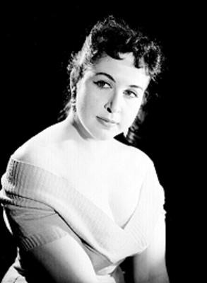Maria Rubio, de perfil tres cuartos, rostro al frente y brazos sobre el regazo, retrato