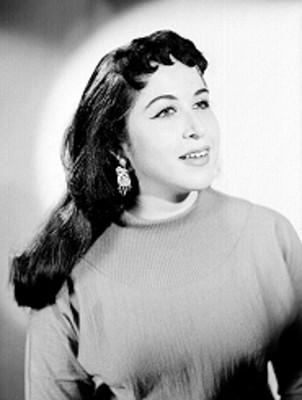 Maria Rubio, sonríe, cuerpo y rostro a su derecha, fondo claro oscuro, retrato