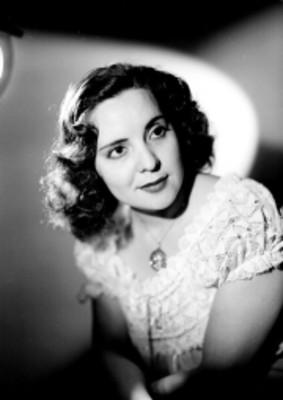 Celia Manzano, sentada en tres cuartos de perfil con blusa de encaje, retrato