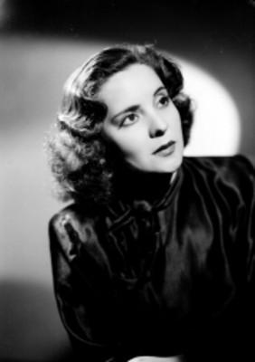 Celia Manzano, con vestido de cuello alto y corbata, fondo mclaro oscuro, retrato