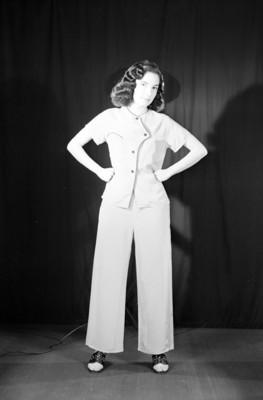 Martha Patricia, actriz, manos a la cintura, viste blusa de botones y pantalón largo, retrato de perfil