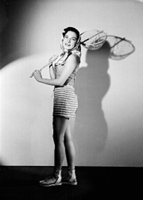 Martha Patricia, actriz, mascada en la cabeza y en las manos un caza insectos, viste de short y blusa, sonríe, retrato