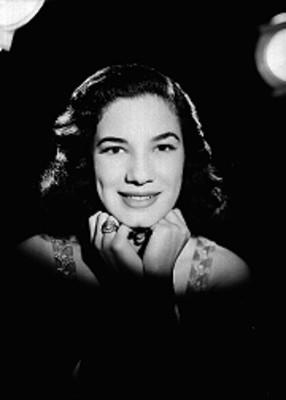 Martha Patricia, sonríe de frente y posa manos bajo la barbilla, fondo oscuro, retrato