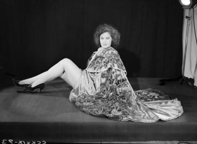 Maria Eugenia Villalobos, sentada al piso con capa y piernas descubiertas, retrato