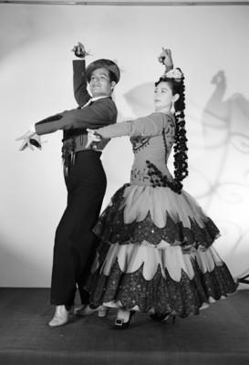 Maria Eugenia Villalobos y acompañante, simulan bailar, con trajes sevillanos, retrato