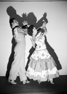 Maria Eugenia Villalobos y acompañante de perfil derecho, palmean en actitud de baile, retrato