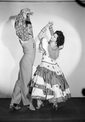 Maria Eugenia Villalobos y acompañante, con trajes sevillanos, simulan bailar, retrato