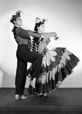 Maria Eugenia Villalobos y acompañante bailan, usan atuendo flamenco y castañuelas, retrato