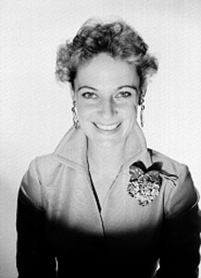 Constance Hool, bailarina de ballet, viste de saco con botones al frente y accesorios, sonríe, retrato de frente