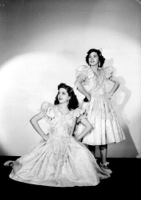 Hermanas Gutierrez, una hincada y otra de pie ambas con las manos en la cadera, portan vestidos largos, sonrien, retrato
