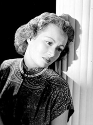 Alicia Ravel, apoya espalda sobre una columna, viste blusa estampada de cuello alto, retrato