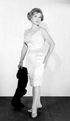 Rebeca San Roman, de pie, con vestido ceñido y estola en mano, retrato