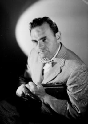 Leo Miller, actor, sentado de costado en una silla con las manos en el respaldo, viste de traje con moño, retrato