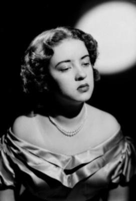 Leticia Valencia, mirada baja, con hombros descubiertos y collar de perlas, retrato