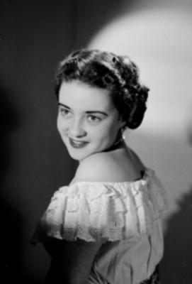 Leticia Valencia, en primer plano, sonríe, fondo claro oscuro, retrato