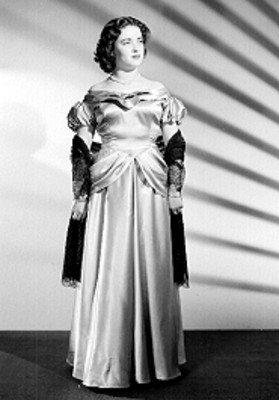 Leticia Valencia, de pie y de frente, con vestido de gala y sombras al fondo, retrato