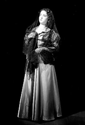 Leticia Valencia, de pie, usa vestido largo con velo sobre cabeza y hombros, retrato