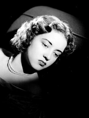 Leticia Valencia, recostada en divan, rostro resaltado, retrato