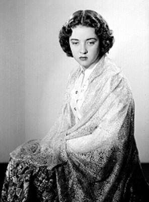 Leticia Valencia, sentada, usa mantilla sobre hombros y brazos, retrato