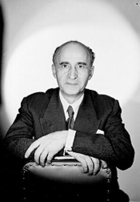 Paulino Masip, escritor, sentado en una silla con las manos apoyadas en el respaldo, retrato de frente