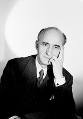 Paulino Masip, escritor, mano a la mejilla en actitud reflexiva, viste de traje y corbata, retrato
