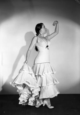 Rosa Norma Reyna, porta vestido de olanes, simula bailar flamenco, retrato de perfil