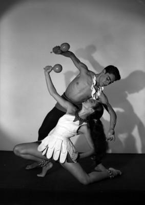 Leonor Mateos y Hugo Romero, ambos con sonajas en mano, simulan bailar, retrato de perfil