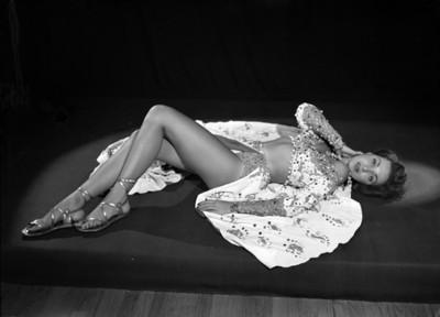 Leonora Amar, vedette, recostada sobre el piso con una mano al rostro y piernas flexionadas, porta vestuario teatral, retrato