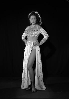 Leonora Amar, vedette, de pie con las manos a la cintura, porta vestuario teatral, retrato de perfil