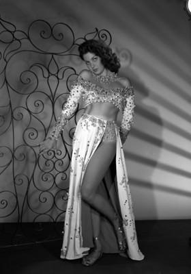 Leonora Amar, vedette, de pie junto a una escenografia, porta vestuario teatral, retrato de perfil