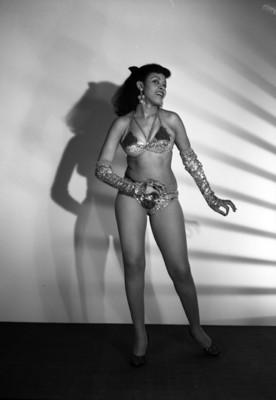 Herminia Alvarez, vedette, porta vestuario teatral, simula bailar, sonríe, retrato de perfil