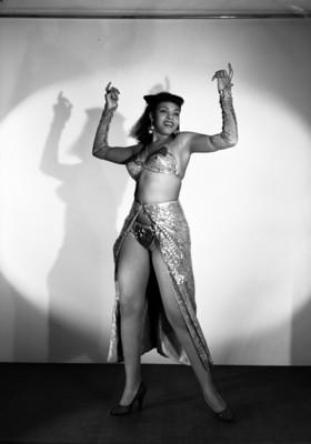 Herminia Alvarez, vedette, manos levantadas y piernas abiertas, porta vestuario teatral, sonríe, retrato de perfil