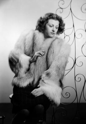 Esther Fernandez, sentada con abrigo de pieles, junto a estructura de espirales, retrato