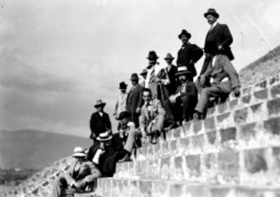 Hombres y mujer en escalinata de edificio prehispánico