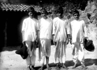 Hombres con vestimenta de manta junto a una casa rústica