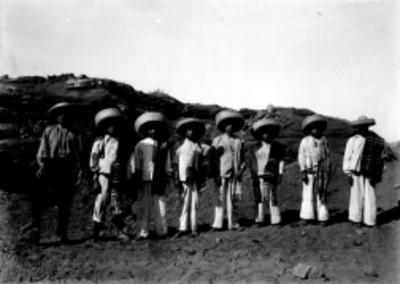 Hombres con indumentaria de manta en unas ruinas, retrato de grupo