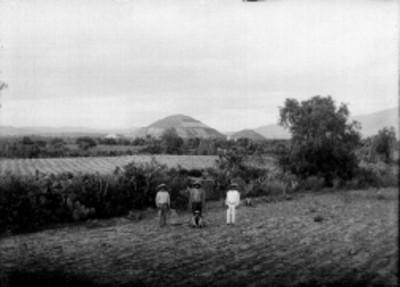 Campesinos en un campo de cultivo al fondo las Pirámides del Sol y La Luna