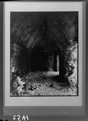 Hombres dentro de arco abovedado en ruinas, reprografía