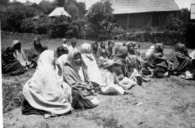 Mujeres y niños purépechas sentados en un patio