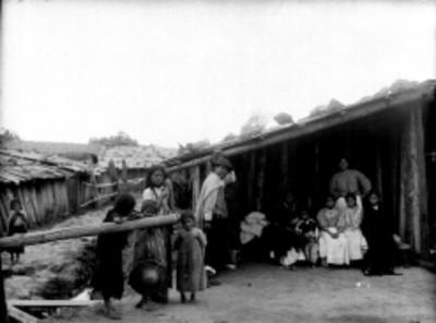Familia indígena en el patio de una vivienda, retrato de grupo